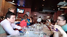Photo: A group of people of various genders and races sitting at a long table inside a restaurant.