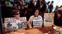 "Nai, Lydia, and Allie sitting at a table, holding signs. Nai has two signs. The first says, ""End the war on Black, poor communities. Justice for Mike Brown."" Then a drawing of a police officer with club and riot gear, based on the image Krip Hop Nation uses for their Police Brutality Profiling mixtape. The second poster says, ""Shooting an unarmed man with hands up 6 times is murder. We all deserve better."" The drawing is Michael Brown with hands in the air. Lydia's sign says, ""Washington Metro Disabled Students Collective in Solidarity with Ferguson. #blacklivesmatter."" Allie's sign says, ""We will not sit idly by. #DisabilitySolidarity for Mike Brown."" Nai and Allie are white. Lydia is East Asian. Nai is wearing dark glasses. Allie is using a manual chair."
